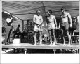 Makaha, 1965. Top finishers in senior men's division: George Downing, center; Fred Hemmings, right, in sun glasses; and Mike Doyle. John Lind, announcing, at far left. Photographer unknown.