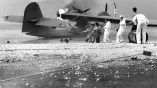 Sailors at Naval Air Station (NAS) Kaneohe, Hawaii, attempt to salvage a burning PBY Catalina