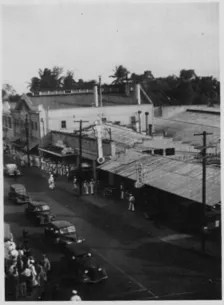 Soldiers and sailors lined up at a business near the bus depot and taxi stand. Building with the gabled facade is the Black Cat-PP-39-6-001