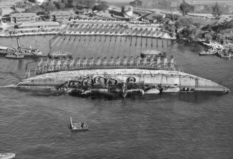 USS_Oklahoma-_Salvage._Aerial_view_toward_shore_with_ship_in_90_degree_position-03-19-43