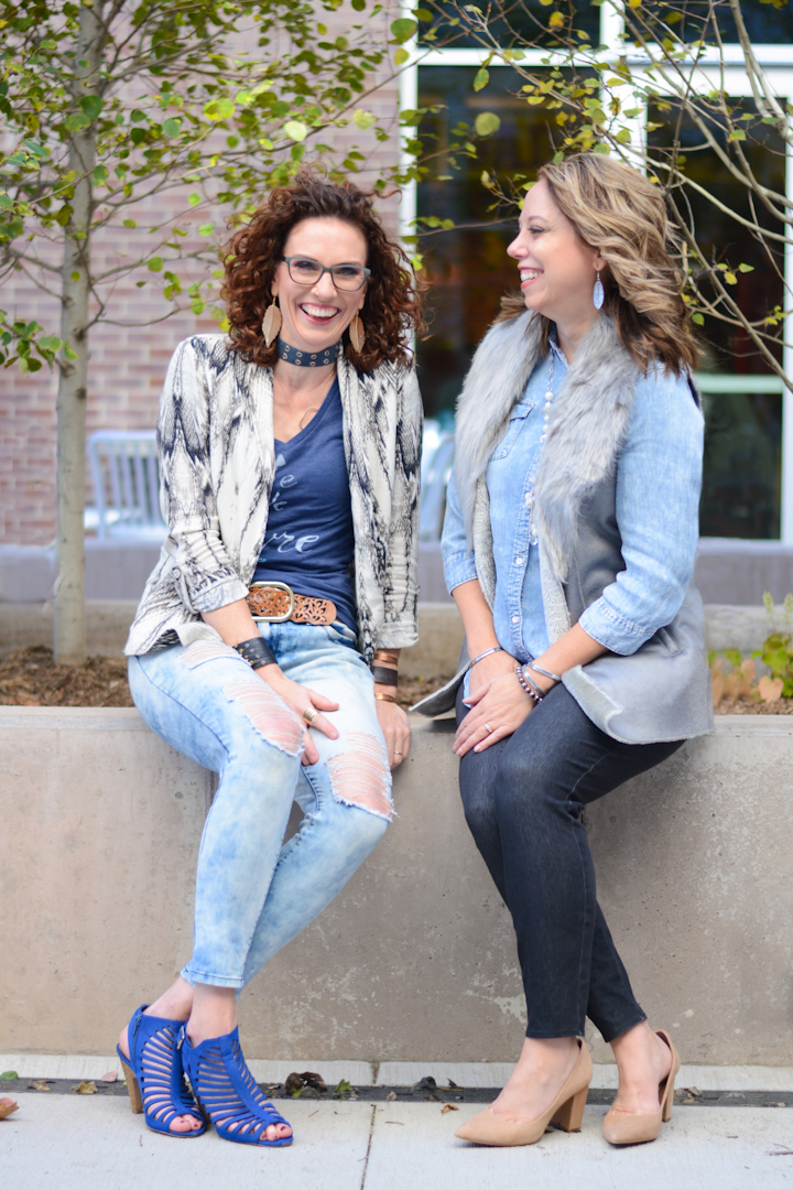 Woman with red, curly hair and glasses and woman with medium bown hair and fur vest sitting on cement bench, laughing. Builidng and trees in background. Bright blue shoes.