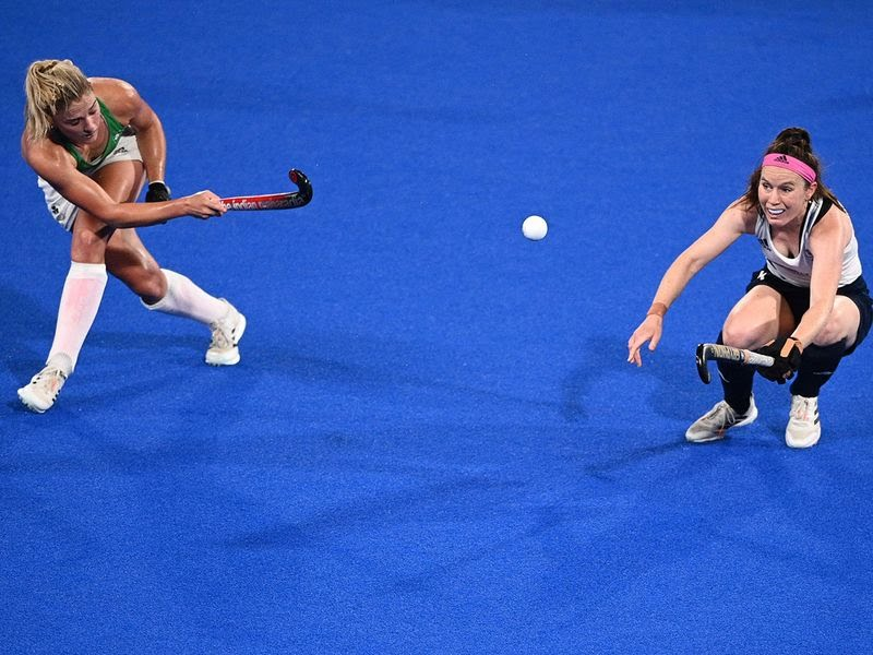 Ireland's Chloe Watkins strikes the ball as Great Britain's Laura Unsworth takes evasive action