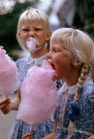 Girls eat large swirls of cotton candy in Copenhagen, Denmark, January 1963.