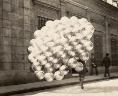 A balloon vendor runs across a road with a trailing mass of balloons in Buenos Aires, November 1921.