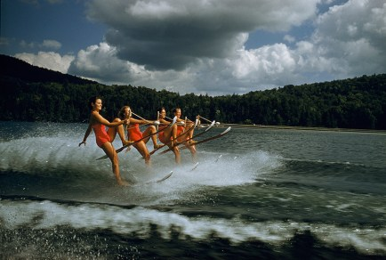 A women's water ski team lifts skis while being towed at 23 mph on Darts Lake in New York, 1956.