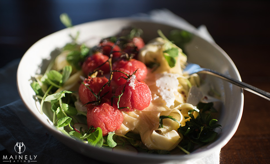 Fresh and light summer pasta with blistered cherry tomatoes, pea shoots and ricotta salata in the lemony herb broth