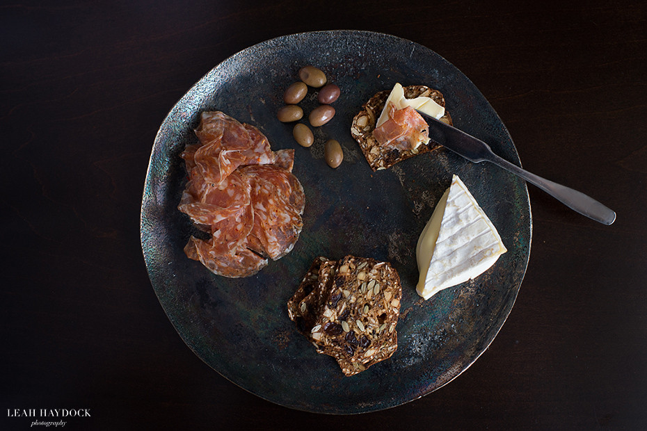 Cheese plate with soppressata, olives and rainforest crisp crackers in salty date and almond