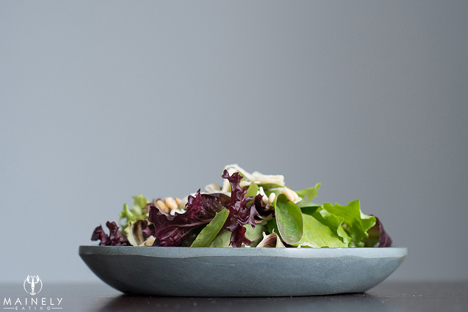 Baby salad leaves with vinaigrette, parmesan shavings and pine nuts