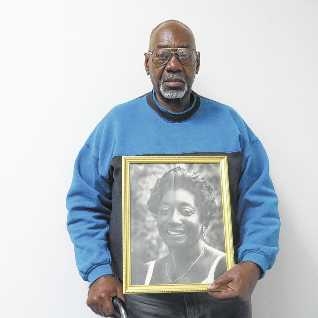 The Rev. Charles Ford holds a photo of his mother, Ada Ford Singleton