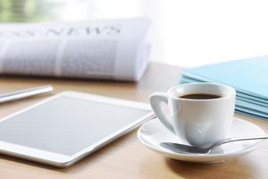 A coffee cup, tablet and newspaper rest on a light wooden surface