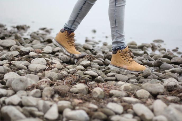 Lower legs, tan boots show as an individual walks across gray rocks