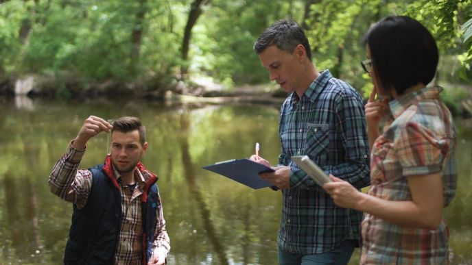 Three individuals stand by a body of water in a wooded area. Two have notebooks and one has a vial of water.