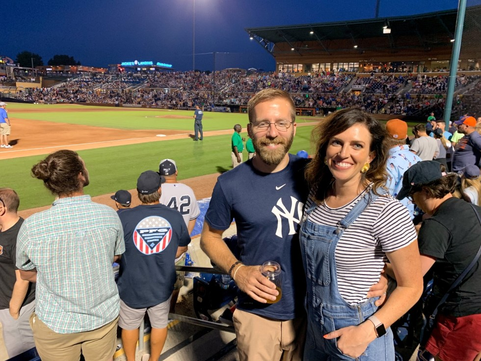 23 Awesome Things To Do in Durham - I'm Fixin' To - @imfixintoblog | Things to do in Durham by popular NC travel blog, I'm Fixin' To: image of a man and woman standing together in the bleachers the Durham Bulls athletic park.