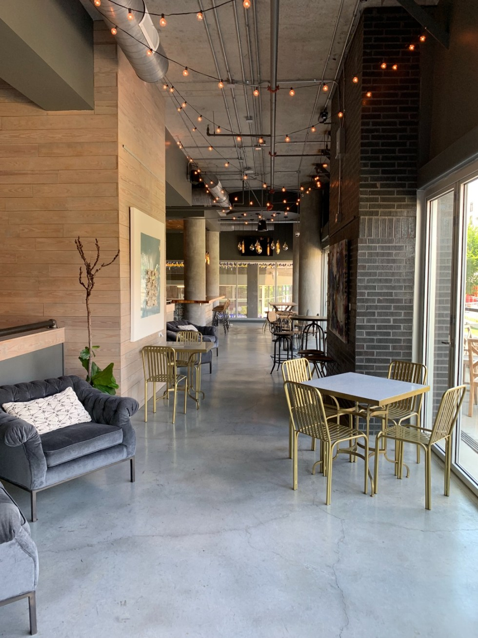 The Ultimate Girls' Day Out in Raleigh - I'm Fixin' To - @imfixintoblog | Girls Day Out In Raleigh by popular NC lifestyle blog, I'm Fixin' To: image of a restaurant with bistro lights, grey velvet tuft chairs, and tables with gold metal chairs.