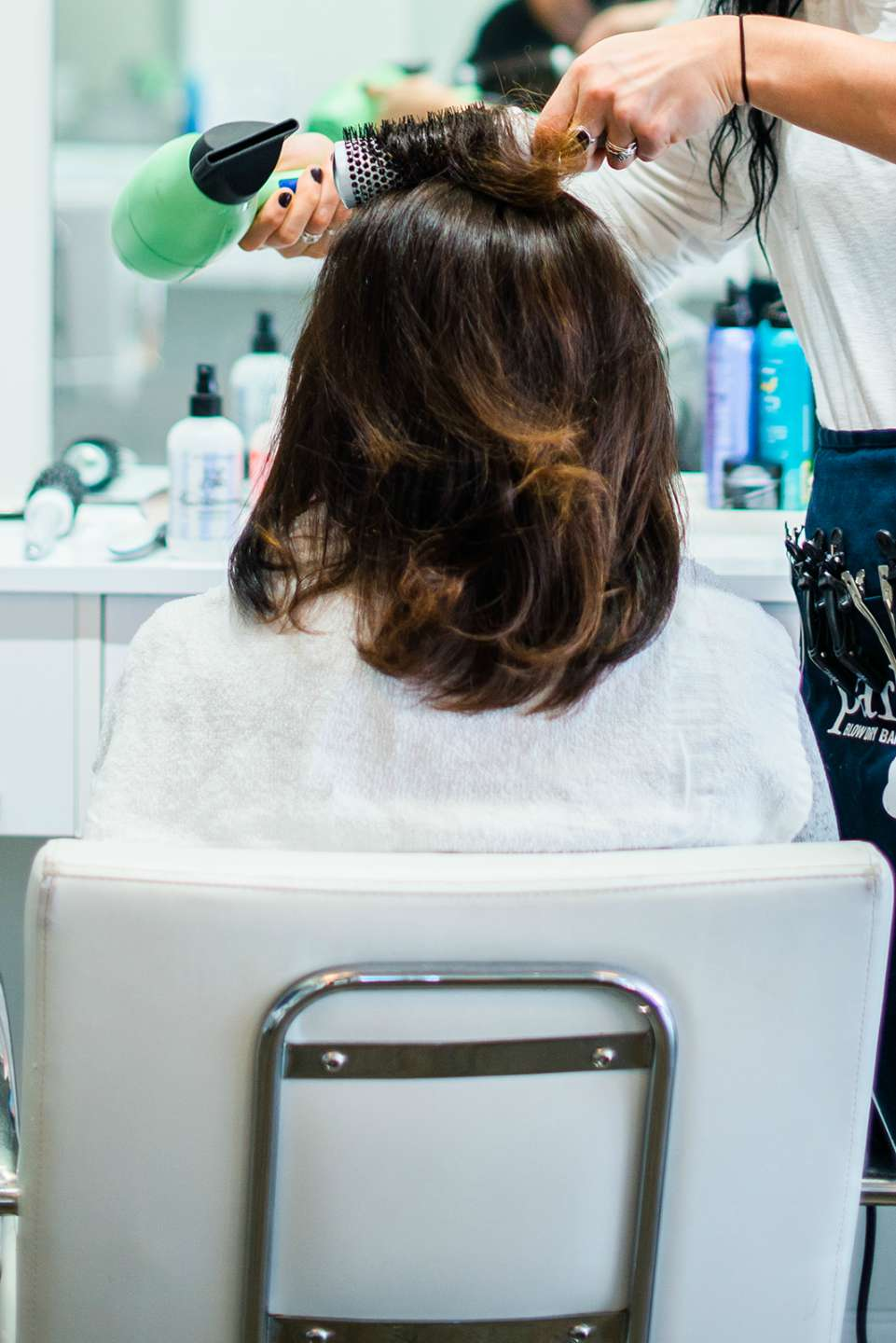 The Ultimate Girls' Day Out in Raleigh - I'm Fixin' To - @imfixintoblog| Girls Day Out In Raleigh by popular NC lifestyle blog, I'm Fixin' To: image of a woman sitting in a white leather chair and getting her hair blow dried.