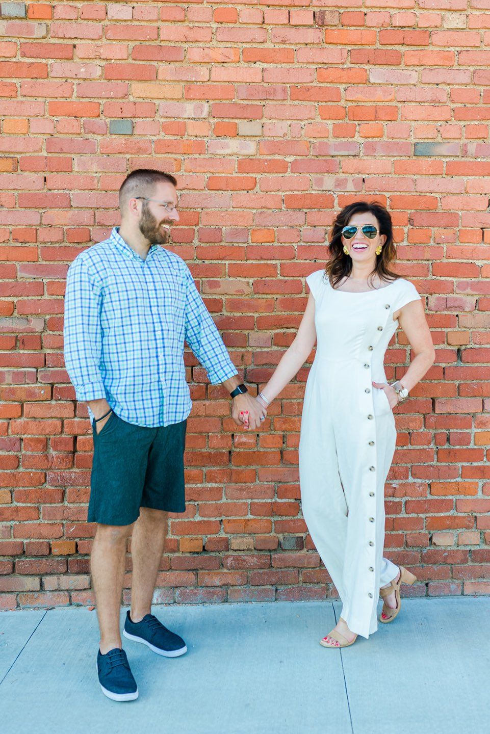 Celebrating 5 Years of Marriage: Lessons Learned - I'm Fixin' To - @mbg0112 | Celebrating 5 Years of Marriage: Lessons Learned by popular North Caroline Life and Style blog, I'm Fixin' To: image of husband and wife standing next to each other outside and holding hands. Woman is wearing a Gal Meets Glam jumpsuit, Nordstrom Ebba Sandal by ONO, Ray-Ban Original Aviator Polarized Sunglasses, and Hunter Blake Earrings.