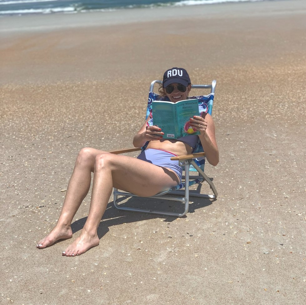 Top 5 Beach Reads for the Summer by popular lifestyle blog, I'm Fixin' To: image of woman wearing purple two piece swimsuit, sitting in a beach chair on the sand, and reading a book.