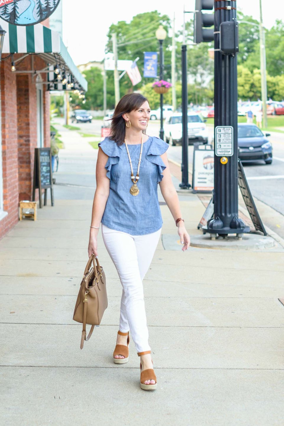 "Three 4th of July Outfit Ideas to Celebrate Independence Day - I'm Fixin' To - @mbg0112 | Three 4th of July Outfit Ideas to Celebrate Independence Day by popular North Carolina life and style blog, I'm Fixin' To: image of a woman walking down a sidewalk and wearing a Escalier Women's Denim Shirt Chambray Tencel V-Neck Jean Shirt Blouse, J. Crew 10"" highest-rise skinny jean in white denim, and Target Women's Morgan Two Piece Espadrille Wedge by Universal Thread."