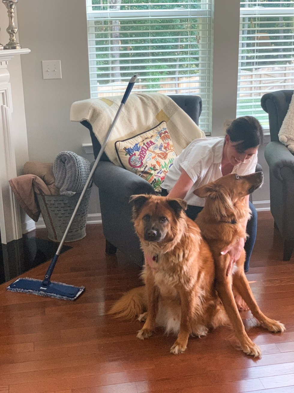 Keeping Our Floors Clean with Bona Essentials - I'm Fixin' To - @mbg0112 | Keeping Our Floors Clean with Bona Essentials by popular lifestyle blog, I'm Fixin' To: image of a woman sitting in an arm chair with her two large dogs at her feet and a Bona Essentials mop propped up against the chair.