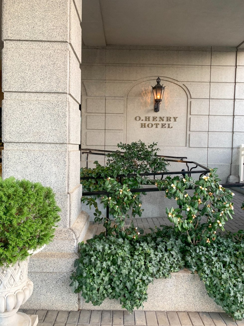 A Night at the O.Henry Hotel In Greensboro, NC - I'm Fixin' To - @mbg0112 |  A Night at the O.Henry Hotel In Greensboro, NC by popular North Carolina blog, I'm fixin' To: image of the exterior of the O. Henry Hotel with green shrub bushes and ivy landscaping.