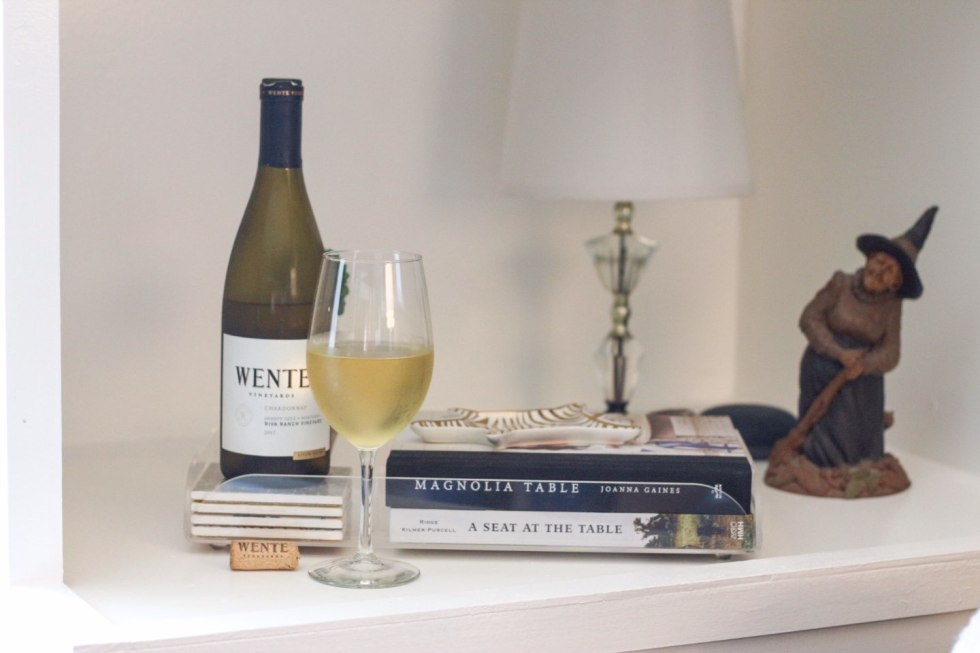 How I Make Time for Decorating with Wente Vineyards - I'm Fixin' To - @mbg0112 | How I Make Time for Decorating with Wente Vineyards by popular North Carolina lifestyle blog, I'm Fixin' To: image of  a bottle and glass of Wente Vineyards wine on a book shelf next to a pile of books.