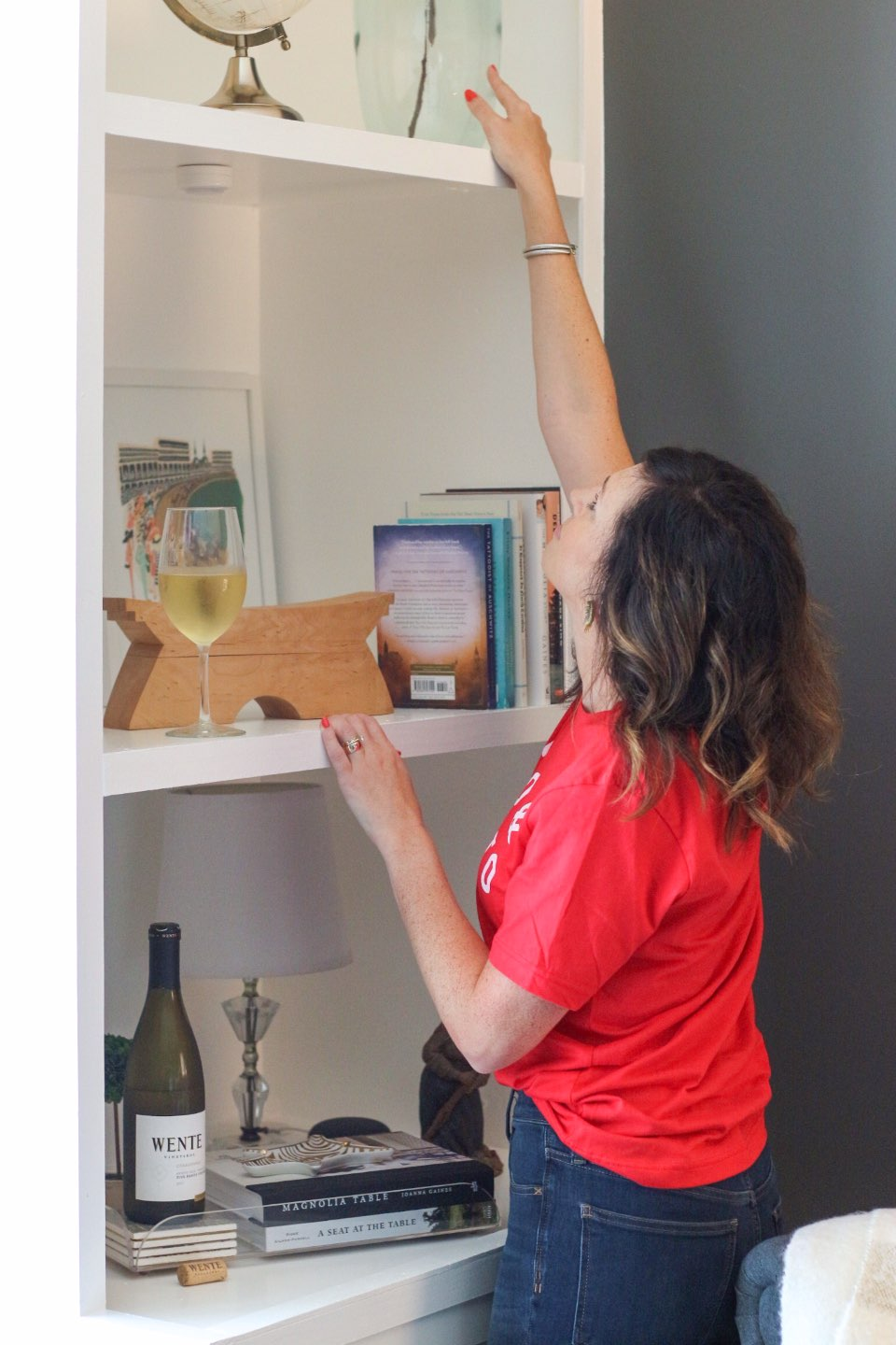 How I Make Time for Decorating with Wente Vineyards - I'm Fixin' To - @mbg0112 | How I Make Time for Decorating with Wente Vineyards by popular North Carolina lifestyle blog, I'm Fixin' To: image of a woman fixing a vase on a shelf in her home with a bottle and glass of Wente Vineyards wine close by.