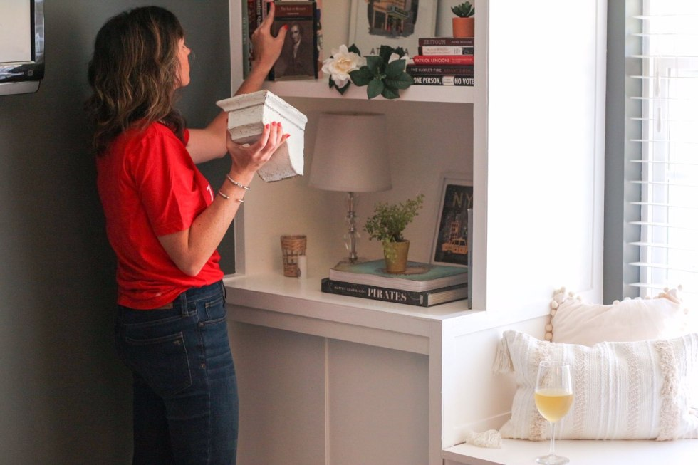 How I Make Time for Decorating with Wente Vineyards - I'm Fixin' To - @mbg0112 | How I Make Time for Decorating with Wente Vineyards by popular North Carolina lifestyle blog, I'm Fixin' To: image of a woman rearranging a book shelf in her home with a bottle and glass of Wente Vineyards wine close by.