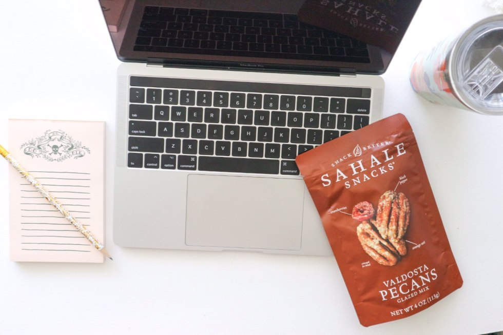 Quick Snack Ideas When You're On the Go by popular NC life and style blogger, I'm Fixin' To: image of an open laptop, notepad and pencil, Rifle Paper Co. tumbler, and a bag of Sahale Snack Valdosta Pecans.