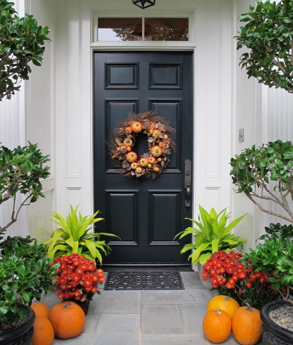 Inspiration Board: Fall Front Porch Ideas - I'm Fixin' To - @mbg0112 | Inspiration Board: Fall Front Porch Ideas by popular North Carolina life and style blog, I'm Fixin' To: image of a front porch decorated with a fall wreath, pumpkins and potted red mums.