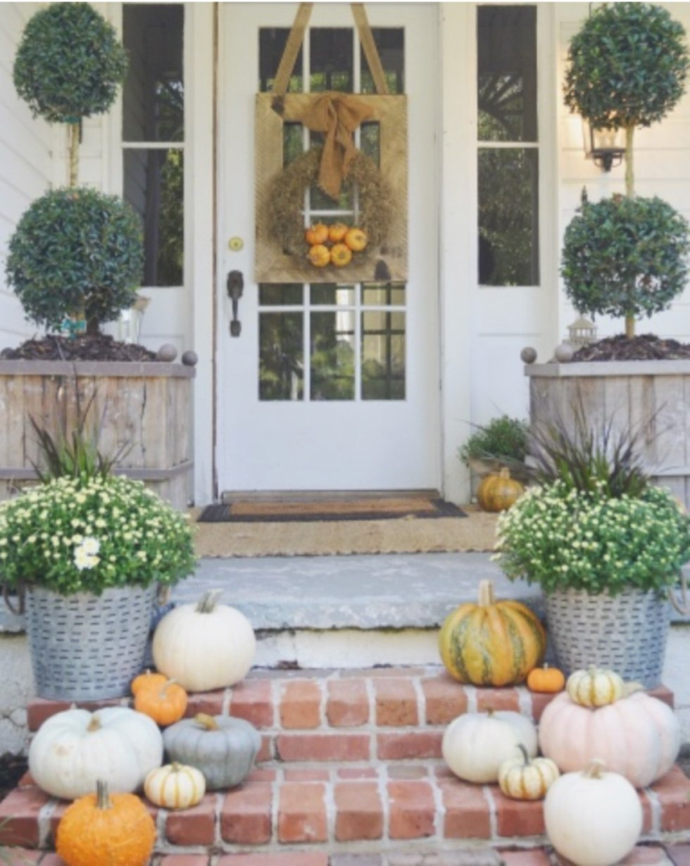 Inspiration Board: Fall Front Porch Ideas - I'm Fixin' To - @mbg0112 | Inspiration Board: Fall Front Porch Ideas by popular North Carolina life and style blog, I'm Fixin' To: image of a front porch decorated with potted white mums, pumpkins, and a fall wreath.