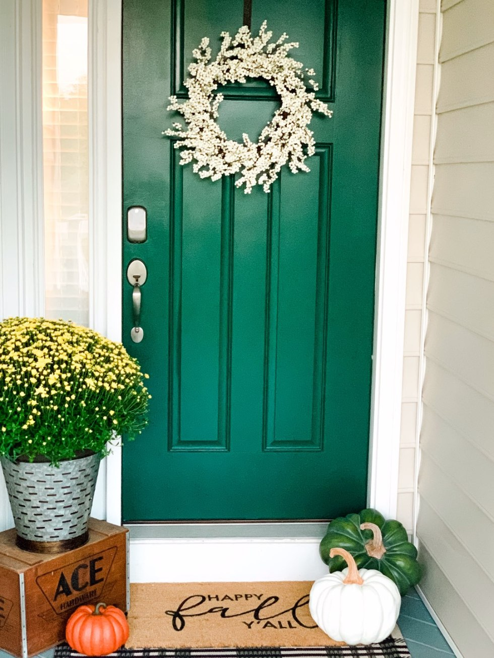 Inspiration Board: Fall Front Porch Ideas by popular North Carolina life and style blog, I'm Fixin' To: image of a front porch decorated with a white wreath, potted yellow mums, and pumpkins.