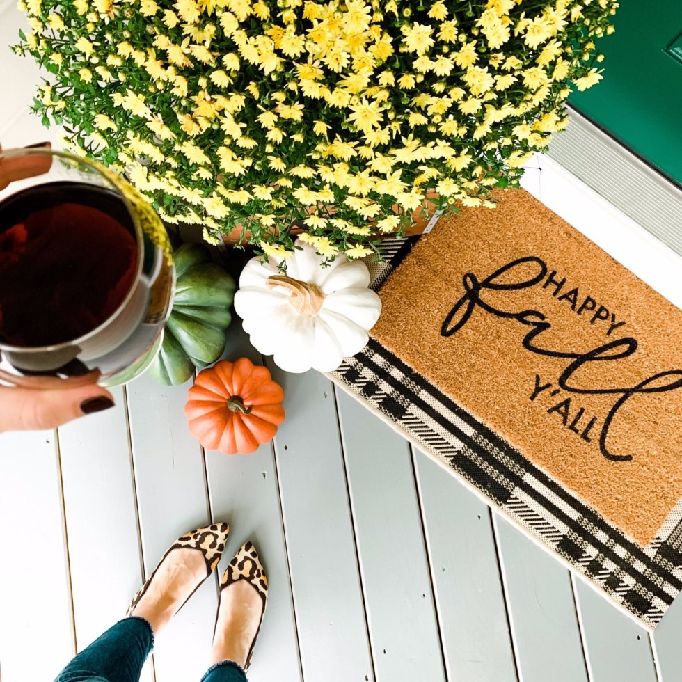 Our Inviting and Cozy Fall Front Porch Decor Ideas - I'm Fixin' To - @mbg0112 | Our Inviting and Cozy Fall Front Porch Decor Ideas by popular North Carolina lifestyle blog, I'm Fixin' To: image of a yellow mums, faux pumpkins, and buffalo plaid door mat.
