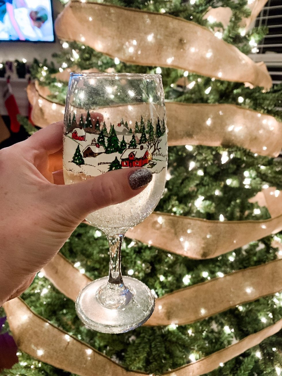 Holiday Home Decor Tour - I'm Fixin' To - @mbg0112 | Holiday Home Decor Tour by popular North Carolina life and style blog, I'm Fixin' To: image of a woman holding a Christmas drinking glass in her hand.
