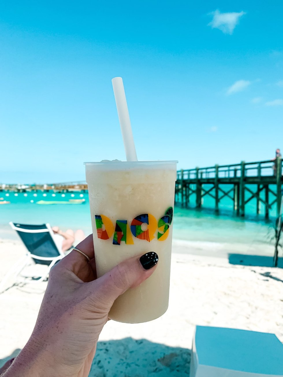 Warming Up in the Bahamas: the Best Things to Do at Baha Mar - I'm Fixin' To - @mbg0112 | Warming Up in the Bahamas: the Best Things to Do in Baha Mar by popular North Carolina travel blog, I'm Fixin' To: image of a woman holding a drink on the beach in the Bahamas.
