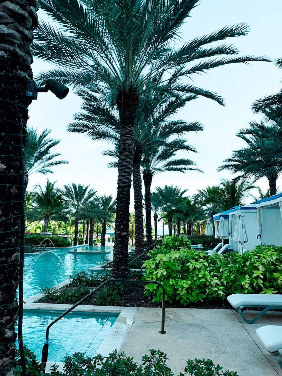 Warming Up in the Bahamas: the Best Things to Do at Baha Mar - I'm Fixin' To - @mbg0112 | Warming Up in the Bahamas: the Best Things to Do in Baha Mar by popular North Carolina travel blog, I'm Fixin' To: image of a swimming pool surrounded by palm trees.