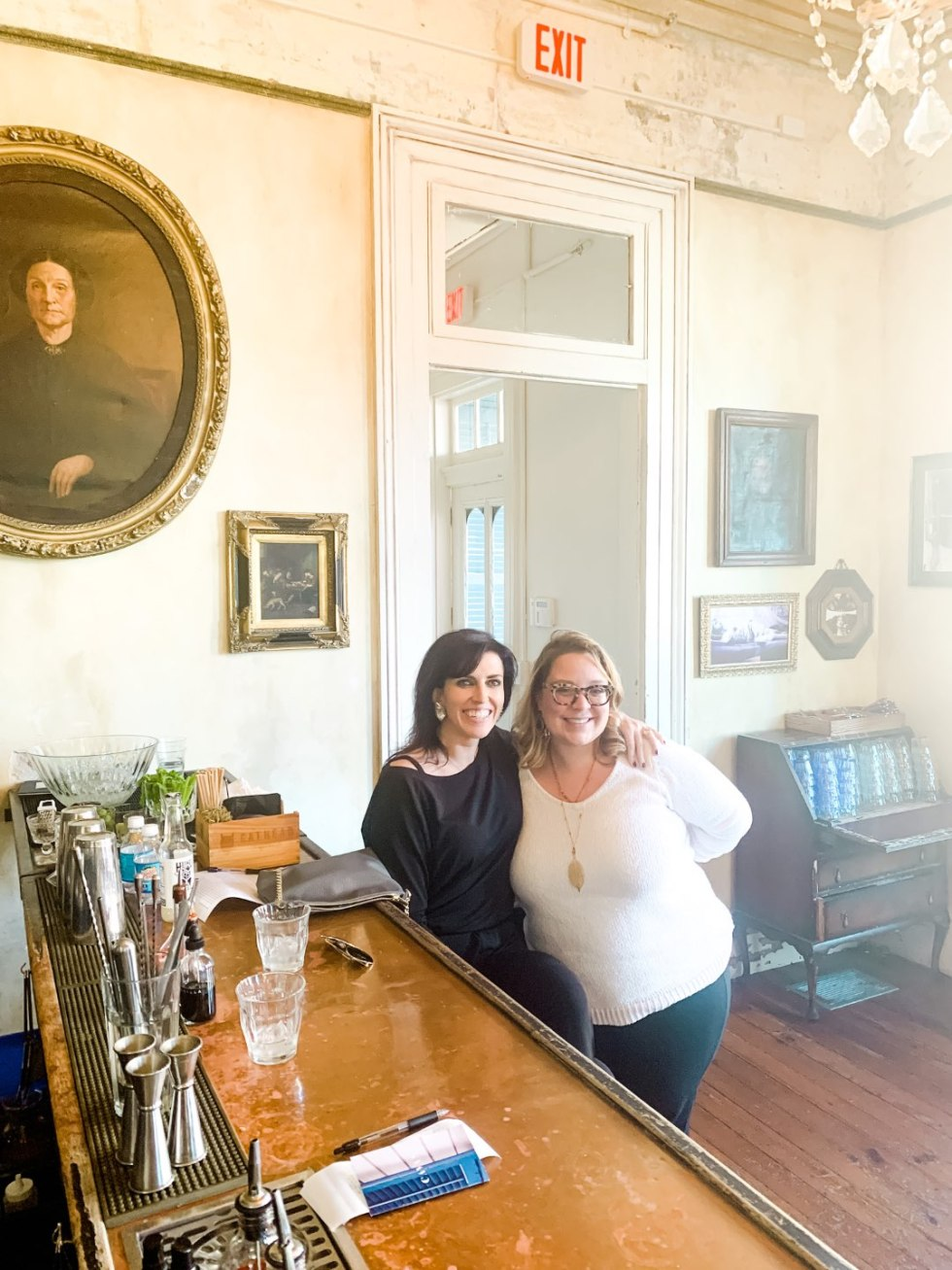 Girls Trip to New Orleans by popular US travel blog, I'm Fixin To: image of two women sitting at a bar at Cavan restaurant.