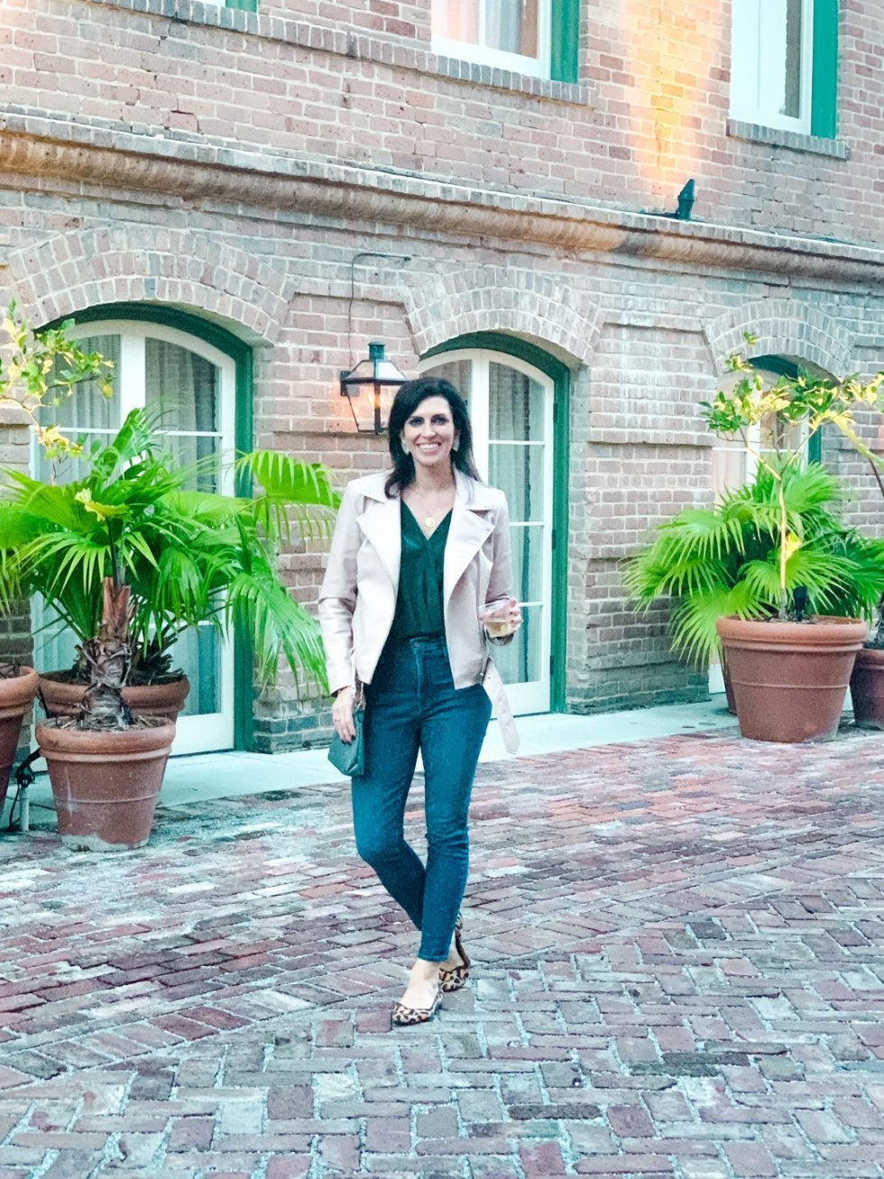 Girls Trip to New Orleans by popular US travel blog, I'm Fixin To: image of a woman wearing a green blouse, faux leather jacket, skinny jeans, and Rothy's shoes.