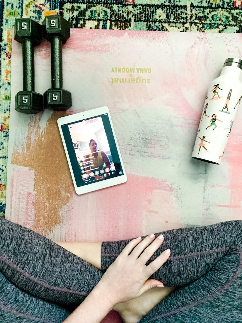 My Favorite Ways to Stay Active While Quarantined - I'm Fixin' To - @mbg0112 | How to Stay Active at Home by popular NC lifestyle blog, I'm Fixin' To: image of a woman sitting on a yoga mat that has a white metal water bottle, 5 lbs hand weights, and a ipad on it.
