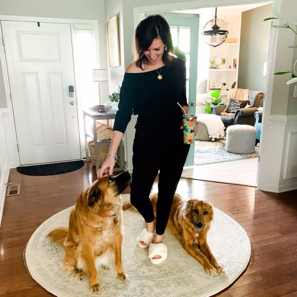 How I'm Learning to Do Nothing - I'm Fixin' To - @mbg0112 | Learning to do Nothing by popular N.C. lifestyle blog, I'm Fixin' To: image of a woman wearing a black jumper and white fuzzy slippers while she stand next to her two dogs in the entryway of her home.