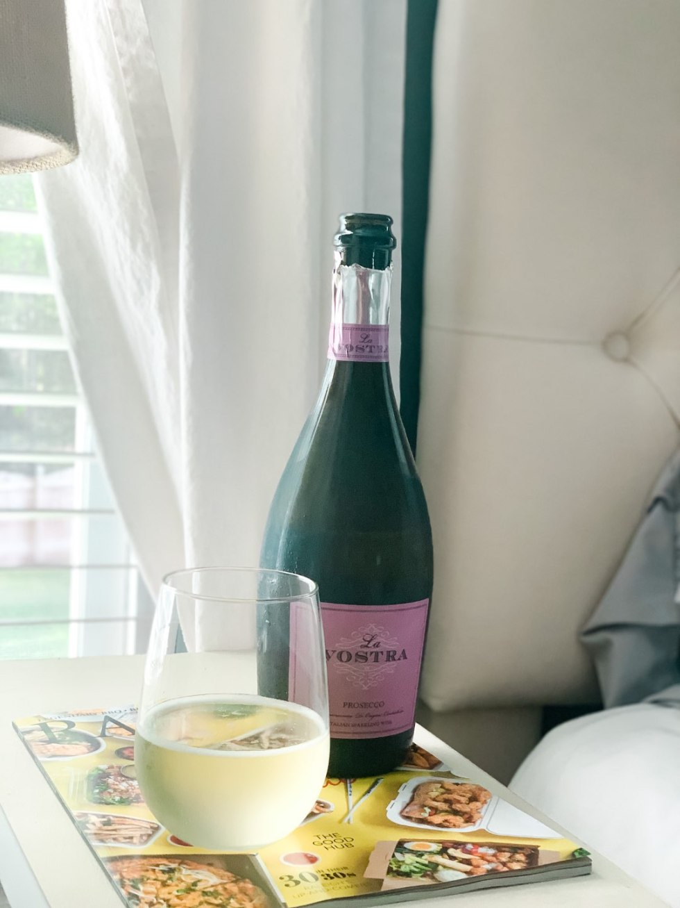 6 Wines to Try While Social Distancing - I'm Fixin' To - @mbg0112 | Top 10 Best Wines by popular N.C. lifestyle blog, I'm Fixin' To: image of a bottle of La Vostra Prosecco on a night stand next to a lamp.
