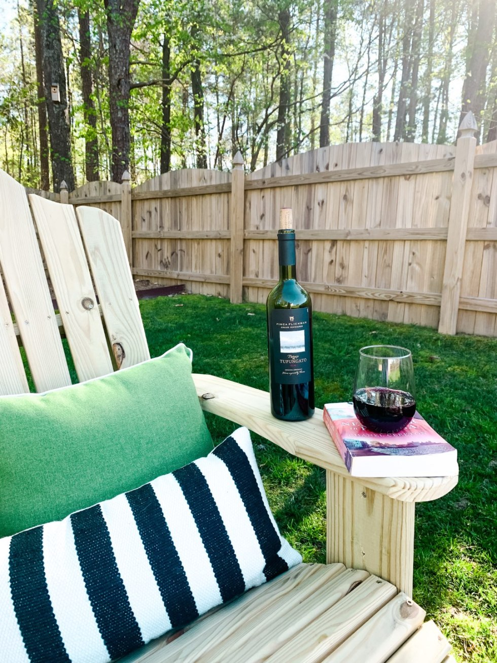 10 Backyard Picnic Essentials - I'm Fixin' To - @mbg0112 | Backyard Picnic by popular North Carolina lifestyle blog, I'm Fixin' To: image of a wooden adirondack chair with a black and white stripe pillow and a green pillow and a book and a bottle of red wine resting on the arm.
