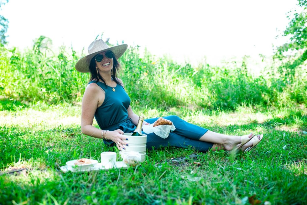 The Top 3 Places to Have a Picnic in Raleigh - I'm Fixin' To - @mbg0112 | Picnic in Raleigh by popular North Carolina blog, I'm Fixin' To: image of a woman sitting on the grass next to a bottle of wine and a croissant and a bagel.
