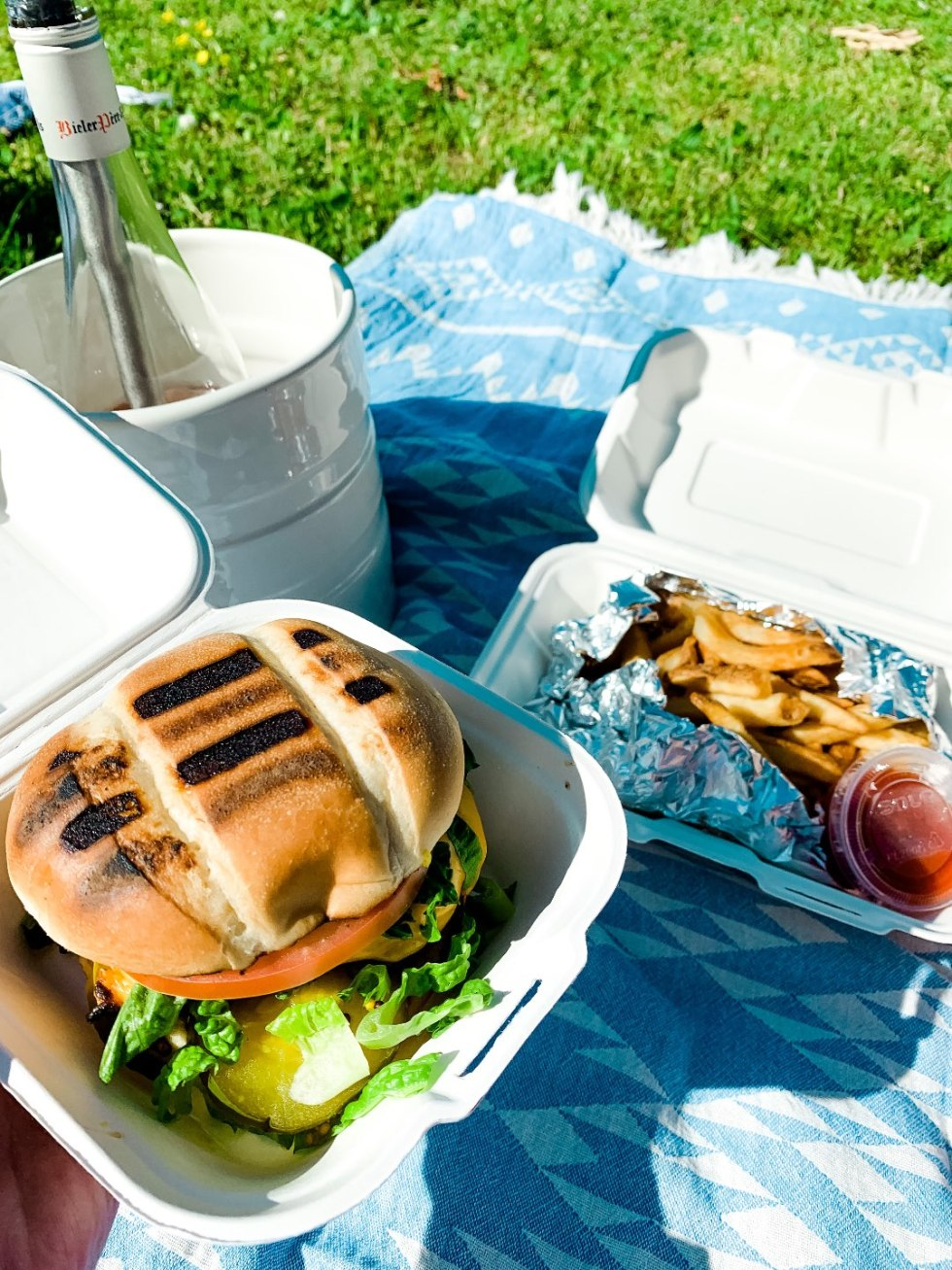 The Top 3 Places to Have a Picnic in Raleigh - I'm Fixin' To - @mbg0112 | Picnic in Raleigh by popular North Carolina blog, I'm Fixin' To: image of a bottle of wine, cheeseburger, and fries on a blue and white tribal print blanket.