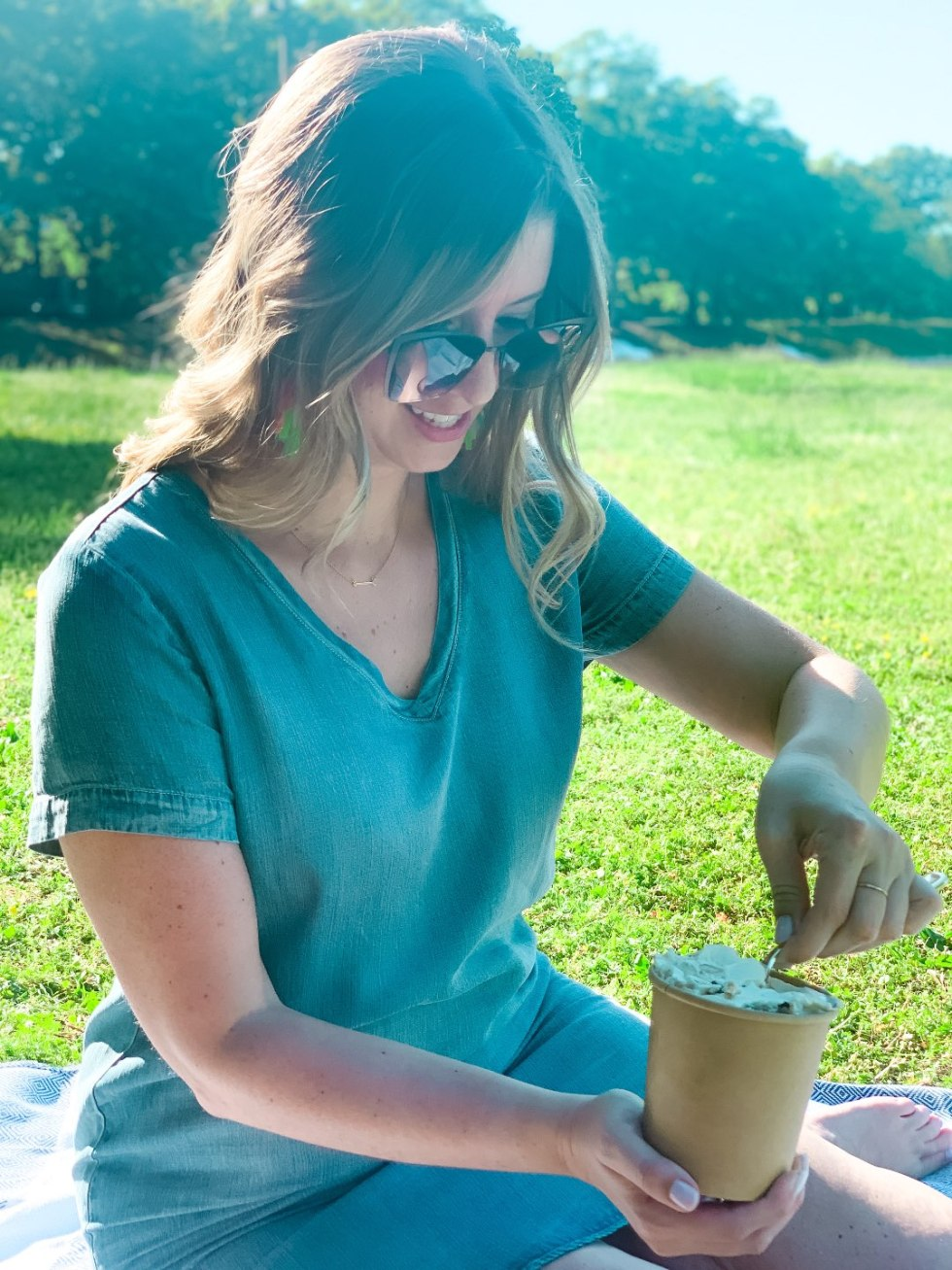The Top 3 Places to Have a Picnic in Raleigh - I'm Fixin' To - @mbg0112 |  Picnic in Raleigh by popular North Carolina blog, I'm Fixin' To: image of a woman sitting on a blue tribal print blanket and eating Two Roosters ice cream.