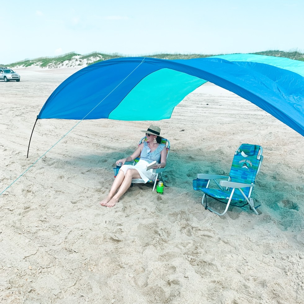 Beach Essentials by popular North Carolina lifestyle blog, I'm Fixin' To: image of a woman wearing a Nordstrom Brixton Joanna Straw Hat while sitting in a Amazon Beach Mall Padded 3 in 1 Lay Flat Aluminum Beach Chair Lounger Recliner with Drink Holder under a Shiubumi Shade.