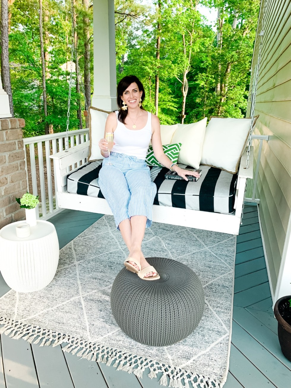 Happy Hour Cocktails by popular North Carolina lifestyle blog, I'm Fixin' To: image of a woman sitting on her front porch swing while holding a gin cocktail and wearing a Women's Slim Fit Any Day Tank Top, Cropped linen beach pant, Amazon Harper Shoes Women's Slip on Flat Slide Band Sandal, and Hunter Blake The WAVE earrings.