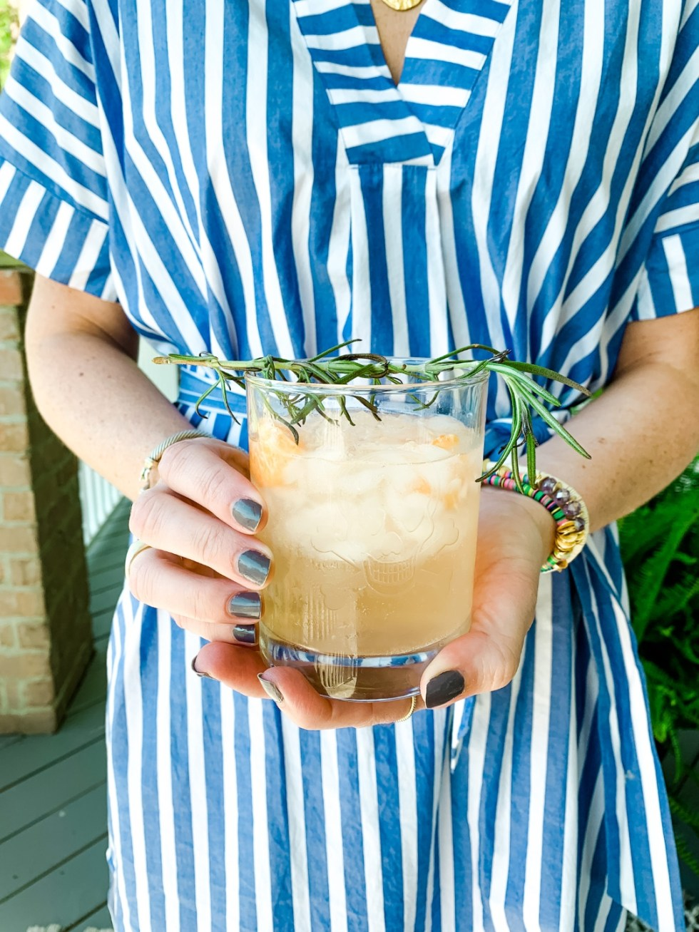 3 Happy Hour Cocktails to Enjoy At Home - I'm Fixin' To - @mbg0112 | Happy Hour Cocktails by popular North Carolina lifestyle blog, I'm Fixin' To: image of a woman standing on her front porch while holding a gin cocktail and wearing a Hart JANUS PENDANT ON LONG LINK CHAIN, Michelle McDowell Tijuana Earrings, and J.Crew Cotton poplin maxi dress in awning stripe.