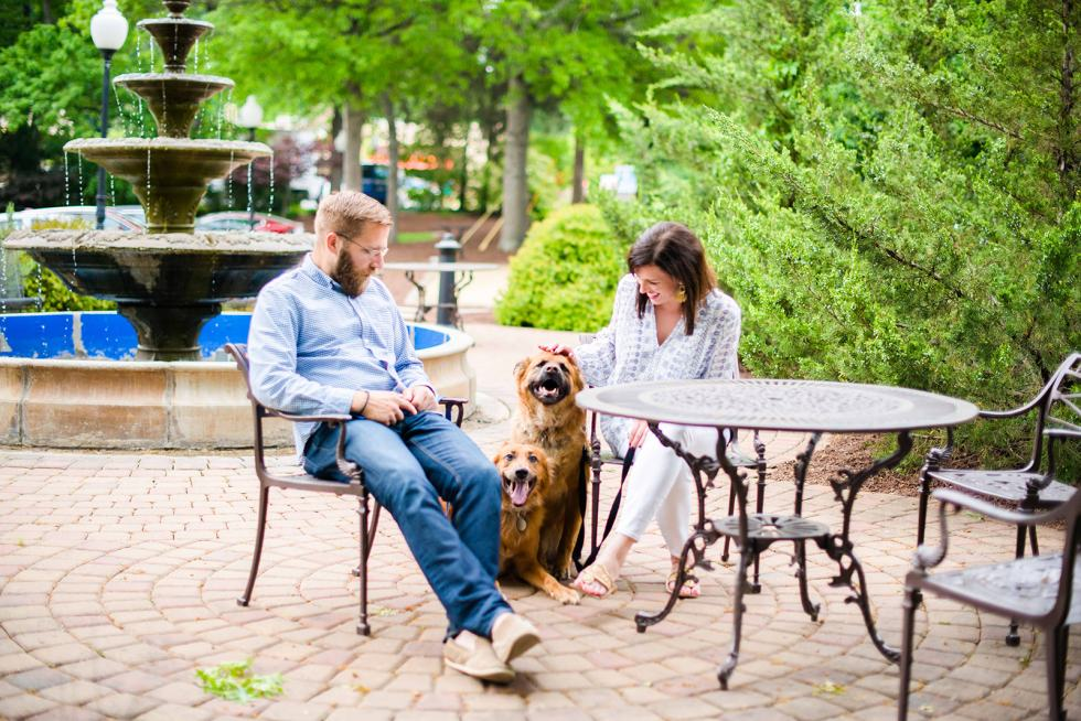 North Carolina Destinations by popular North Carolina blog, I'm Fixin' To: image of a man and woman sitting outside by a fountain with their two dogs.