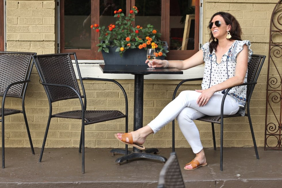 Fun Things to do in the Summer by popular North Carolina lifestyle blog, I'm Fixin' To: image of a woman sitting at a table and drinking a glass of white wine.