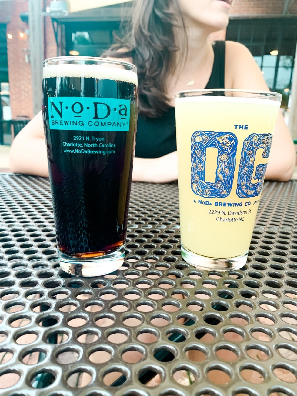 Weekend in Charlotte: Best Breweries and Places to Eat - I'm Fixin' To - @mbg0112 | Weekend in Charlotte by popular N.C. travel blog, I'm Fixin' To: image of a woman sitting in front of two glasses of beer at NoDa Brewing Company.